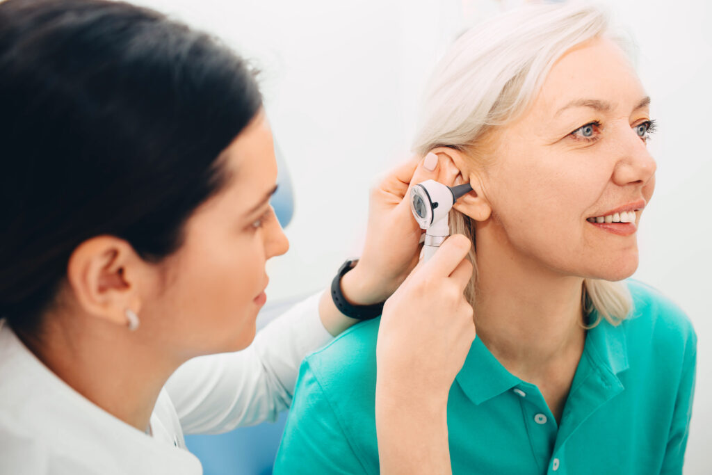 Mature woman getting ear exam at clinic